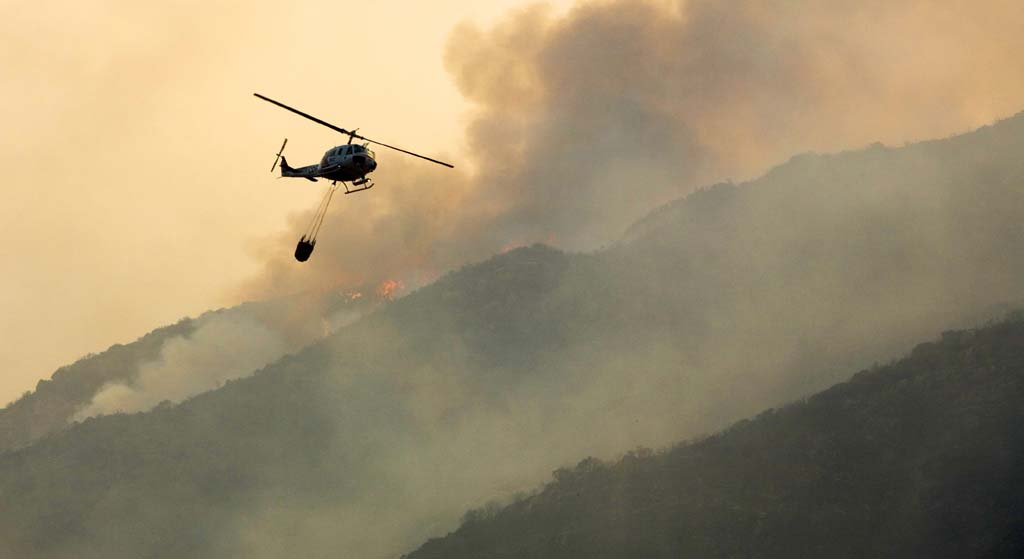 The collections for wildfire fees issued by Cal Fire is being postponed following thousands of complaints over the fees legality from state residents. The fees are supposed to be used for fire prevention activities. Above, a helicopter prepares to drop water on flames during the Witch Creek Fire in October 2007. Photo by Daniel Knighton