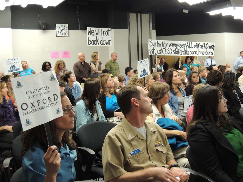 """OPA supporters who attended the San Diego County Board of Education meeting on April 10 held up signs with messages including, """"We will not back down,"""" and """"Sue Hartley, you represent ALL of North County, not just CUSD staff and its board members."""" Photo by Rachel Stine"""