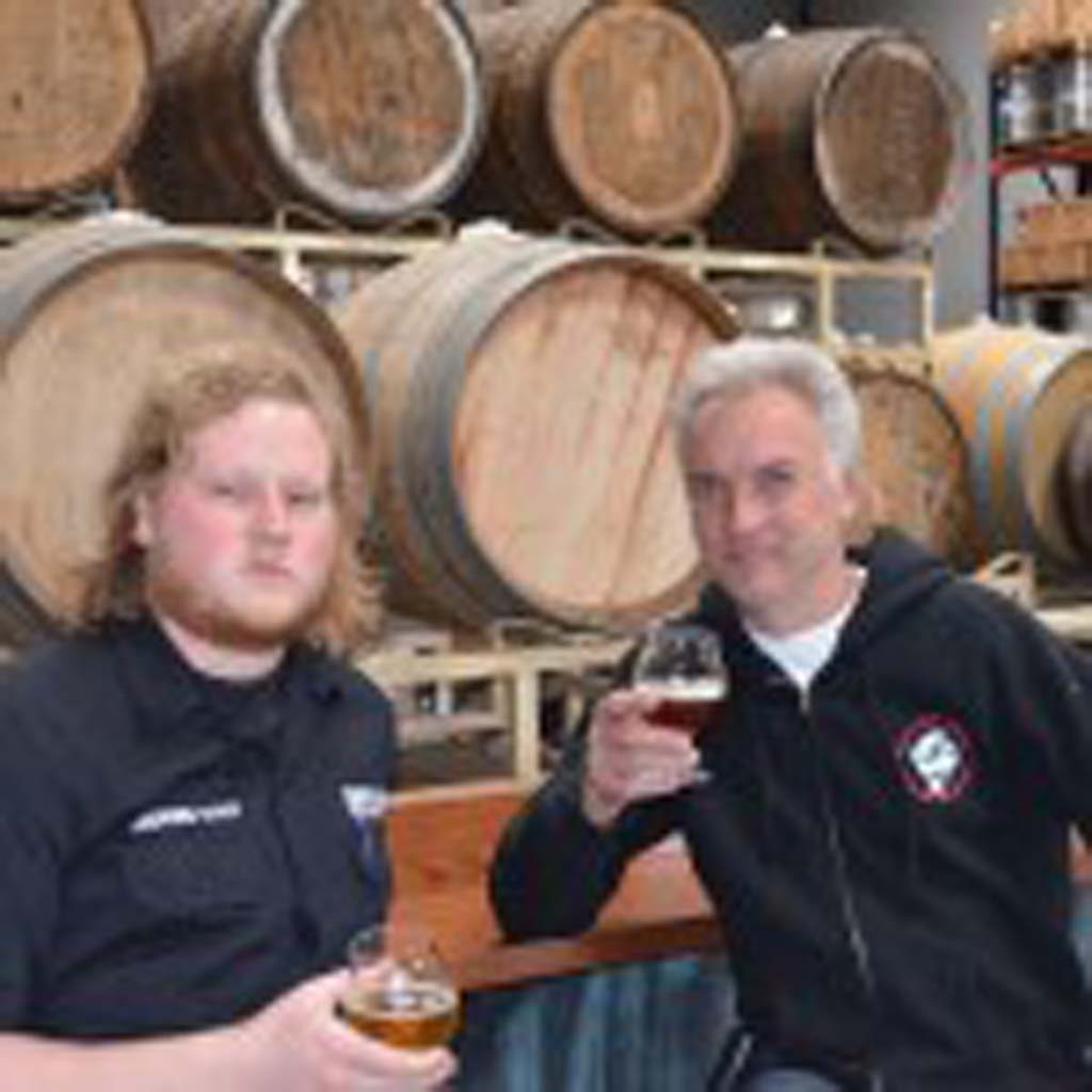 Brandon Sieminski, left, holds Iron Fist Brewery's renegade blond and his dad, Greg, grips a Belgian Dubbel. The Sieminskis operate Iron Fist, one of the craft breweries responsible for Vista's rapidly expanding beer scene. Photo by Jared Whitlock