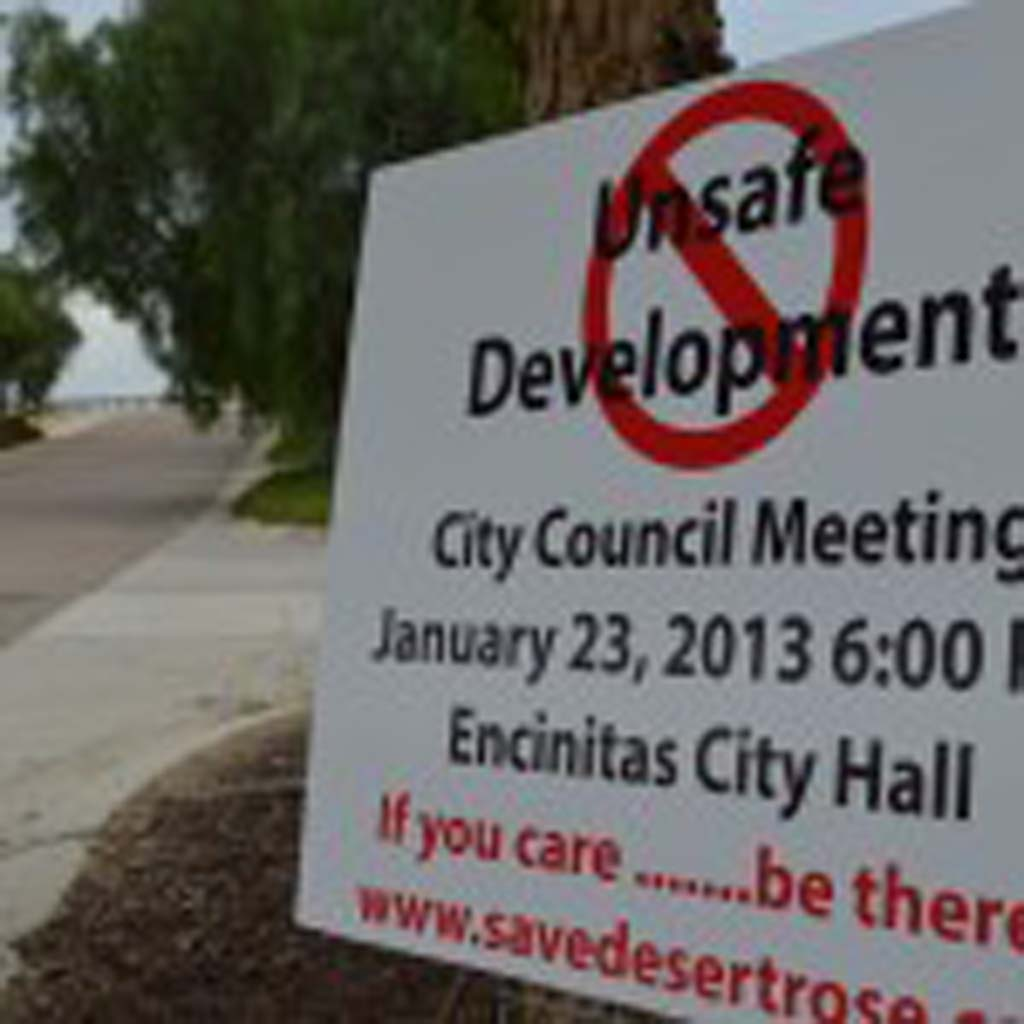 """A sign staked in northeastern Olivenhain at the beginning of the year urges residents to speak out against the """"Desert Rose"""" development at a City Council meeting. The project was ultimately approved by councilmembers in March. After a long battle at the city level, the Desert Rose debate will play out in court. Photo by Jared Whitlock"""