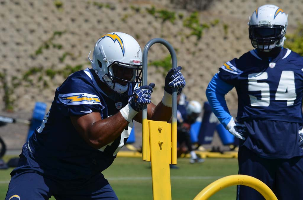Rookie linebacker Devan Walker hits the sled as second year linebacker Melvin Ingram watches on. Photo by Tony Cagala