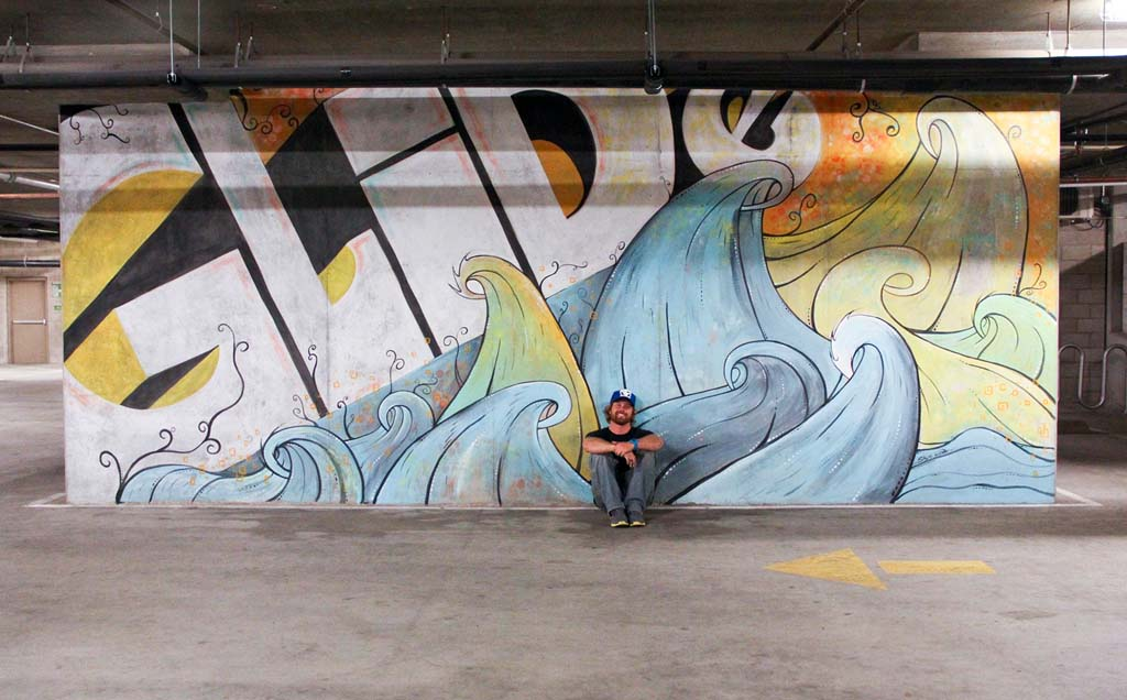 "Artist Skye Walker with his 24-foot ""Glide"" mural at Whole Foods in Encinitas. (Courtesy photo.)"