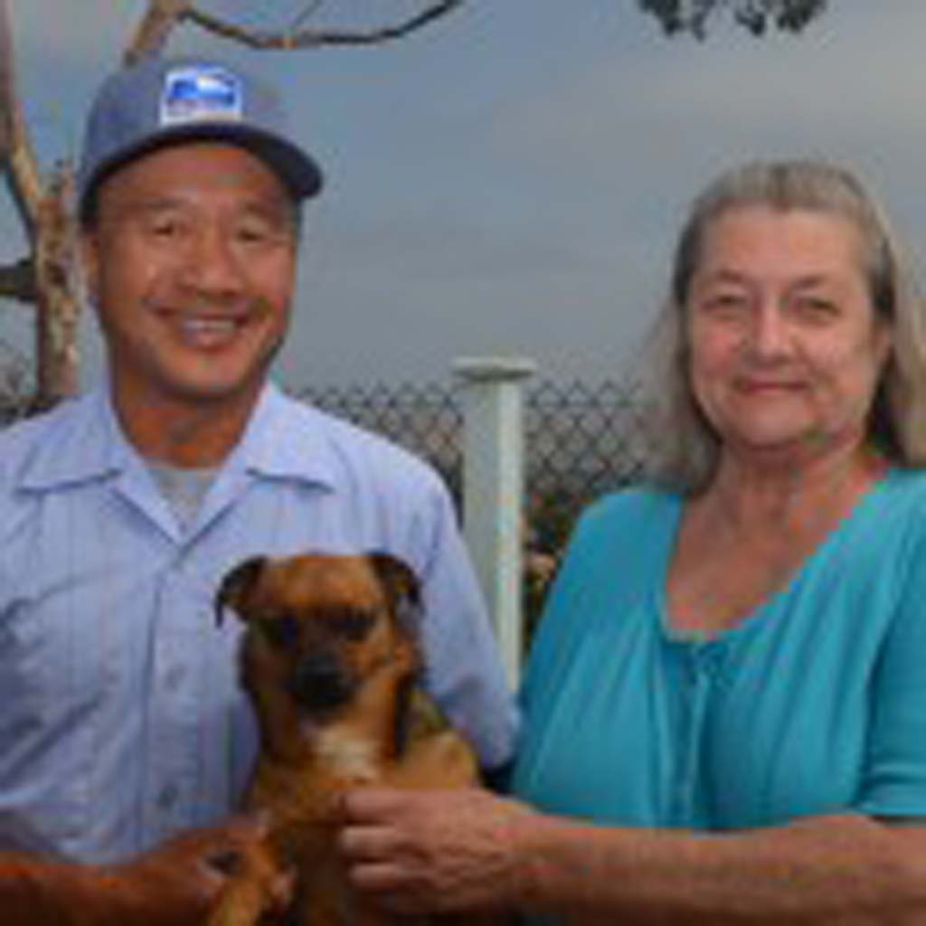 """From left, Mike Tom, Lucky and Helena Cwiek stand together at Cwiek's home in Oceanside. Cwiek calls Tom her """"Guardian Angel,"""" for saving her life. After threatening suicide, Tom made her promise every day for two weeks straight that she wouldn't do anything foolish. Photo by Tony Cagala"""