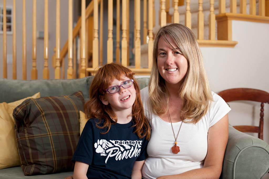 Poinsettia Elementary parent Laura Bodensteiner sits with her 6-year-old daughter Gretchen in their home in Carlsbad. Bodensteiner set up an online donation website to help keep art classes at her daughter's school. Photo by Paige Nelson