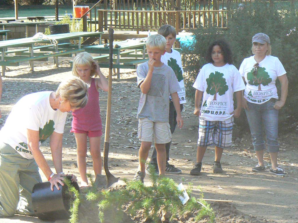 Director of Bereavement Ti Johnson plants a memorial tree with children at Camp H.O.P.E. Courtesy photo