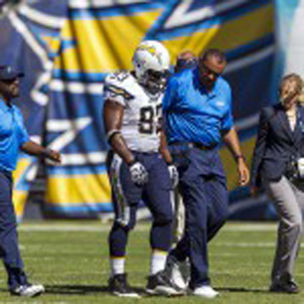 Chargers line backer Dwight Freeney is escorted off the field after injuring his quad Sunday against the Cowboys. Photo by Bill Reilly
