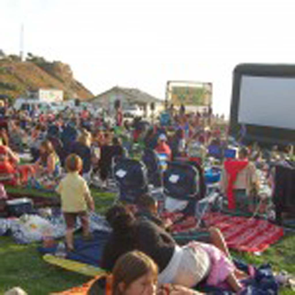 "Hundreds of people gathered at Fletcher Cove Park on Aug. 24 for the ninth annual Beach Blanket Movie Night, which included music by Aloha Radio, snacks, a raffle and this year's feature film, ""Chasing Mavericks."" Photo by Bianca Kaplanek"