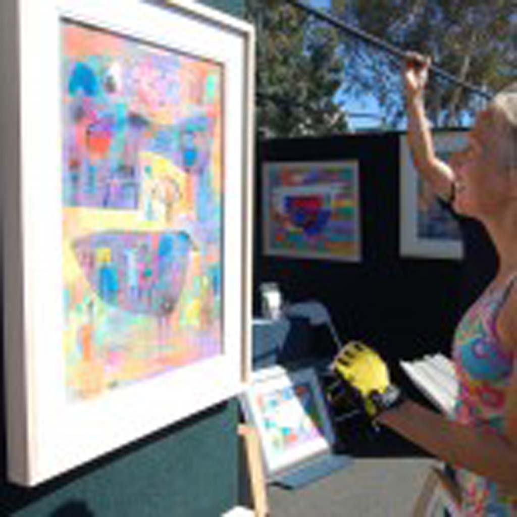 Jill Malone, from Cardiff-by-the-Sea, admires the works of Mario Cespedes. Photo by Bianca Kaplanek