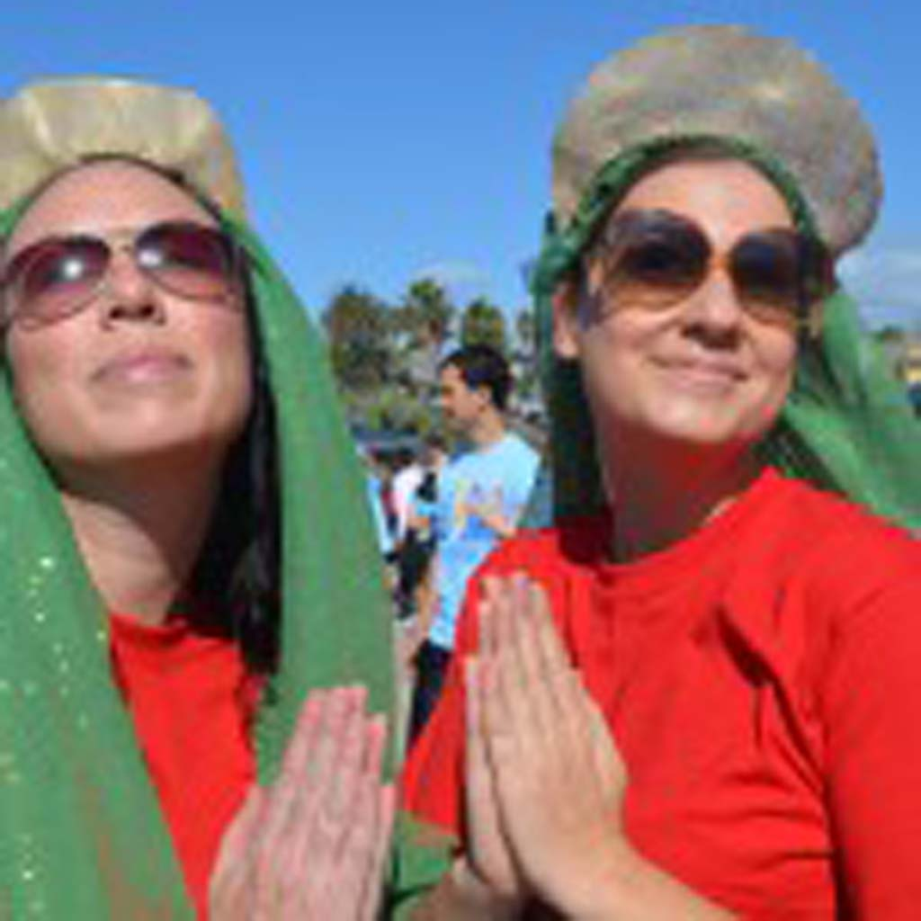 Erin Callaghan, left, and Holly Martin dress in the likeness of the Surfing Madonna during the inaugural Save the Ocean race at Moonlight Beach.