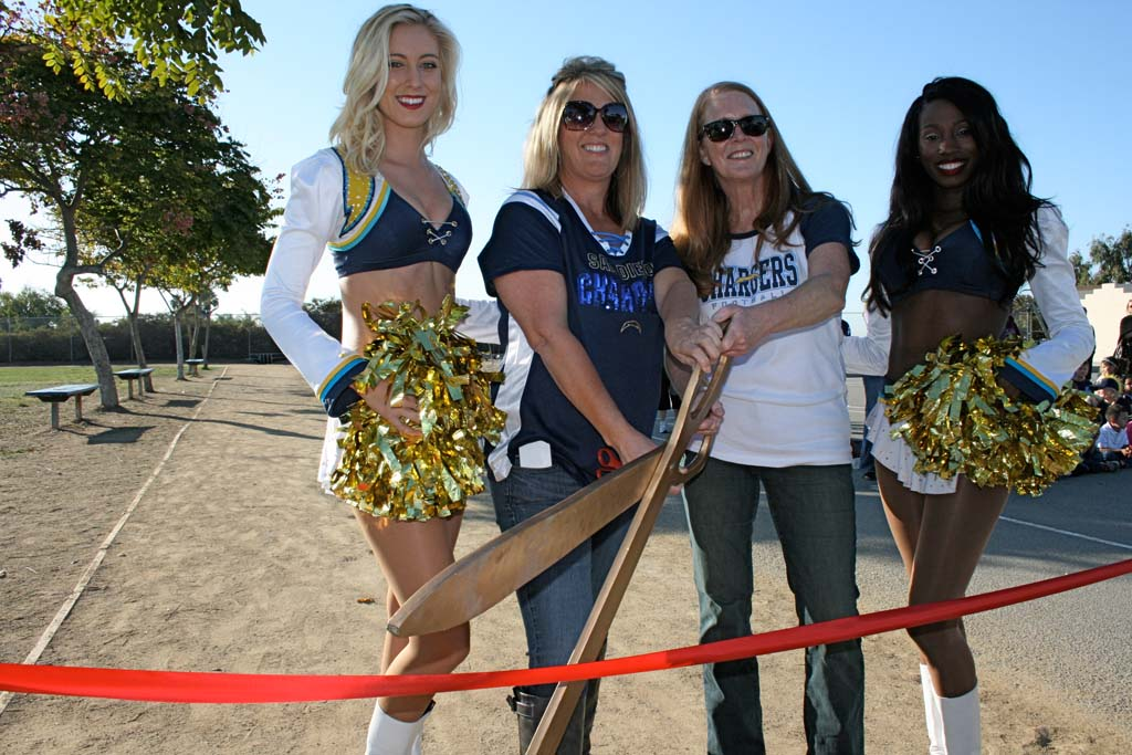 (Left to right) Chargers cheerleader Katie, PTA president Melissia Brohamer, principal Betsy Wilcox, and cheerleader Tinaiya cut the ribbon to celebrate the new school track. The $17,000 track was funded with a Chargers Champions grant. Photo by Promise Yee