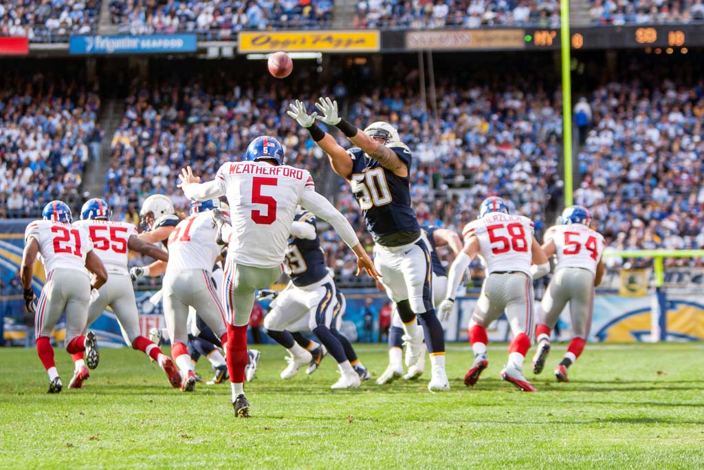 Chargers line backer Manti Te'o (50) comes close to blocking a punt by Giants punter Steve Weatherford (5). The Chargers went on to beat the Giants 37 - 14.