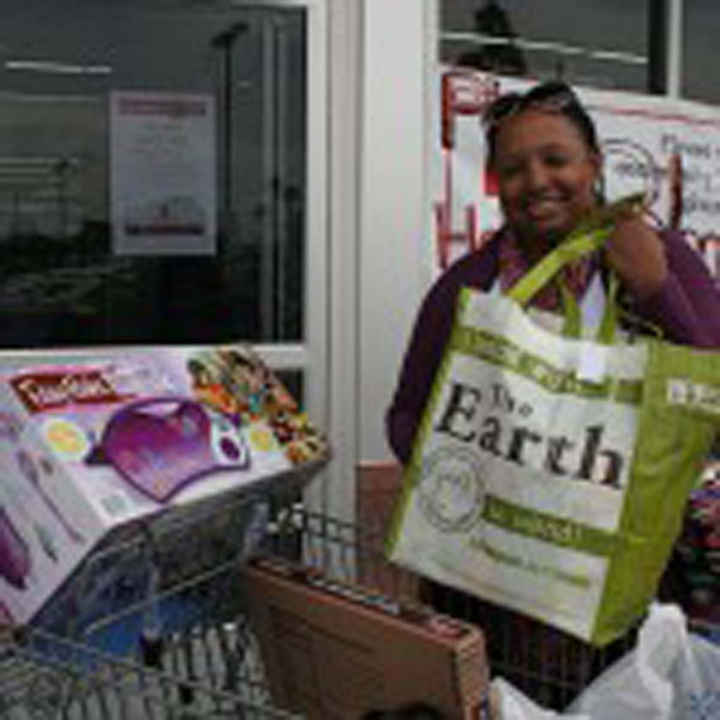 Christine Hayes of Oceanside, shows off that she uses reusable bags whenever she shops. The message of Day Without a Bag is reduce first, then recycle. Photo by Promise Yee