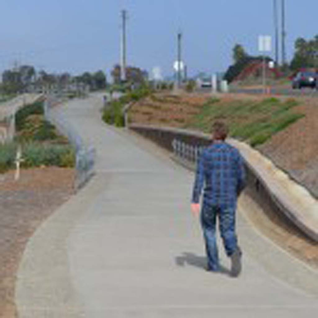 A pedestrian walks along the first sliver of the Encinitas rail trail near the Santa Fe undercrossing. In response to residents' concerns, planning officials would like to find a balance that minimizes rail trail fencing, without eliminating parking. Photo by Jared Whitlock