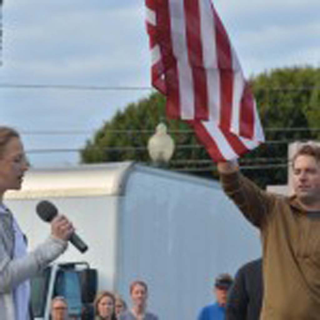 Chloe Lebherz, left, sings the National Anthem before the start of the race. Photo by Tony Cagala