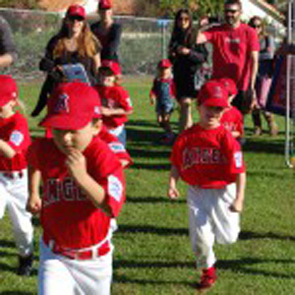 The T-ball Division Angels, made up of players between the ages of 4 and 6, enthusiastically take the field for the parade of teams during Solana Beach Little League's opening day ceremonies March 8. Photo by Bianca Kaplanek