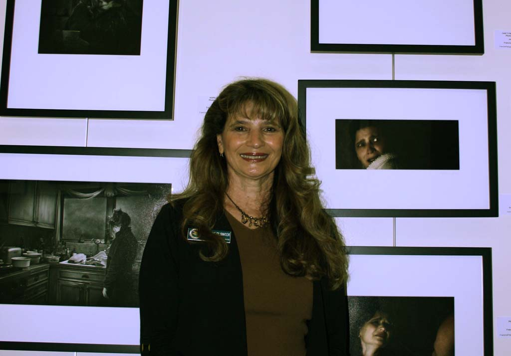 """Photographer Francine Filsinger in front of her work. """"Aftermath"""" is a collection of photos that tells the story of isolation and abuse. Photo by Promise Yee"""