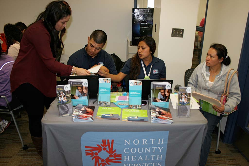 Cheryl McMahen, NCHS outreach coordinator, and Luis Godoy and Janet Osorio, both NCHS outreach workers, review enrollment forms. Californians are required to have healthcare coverage by March 31. Photo by Promise Yee