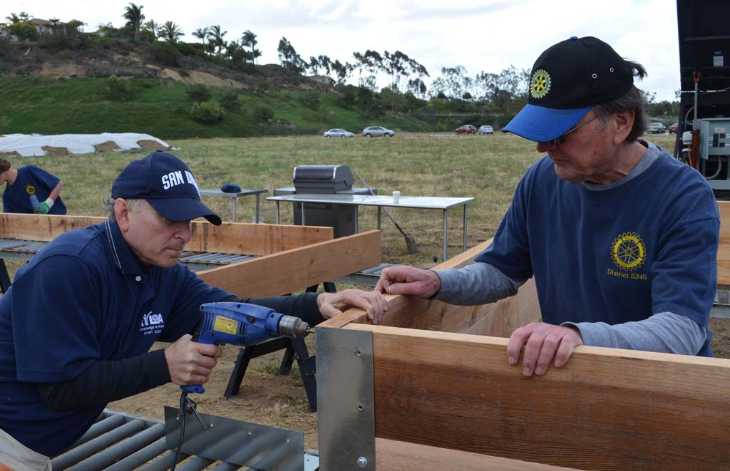 Ron Lieberman (left) drills wood slats together with the help of fellow rotarian Norm Nyberg. They built raised planter boxes for the Encinitas Community Garden. Photos by Jared Whitlock