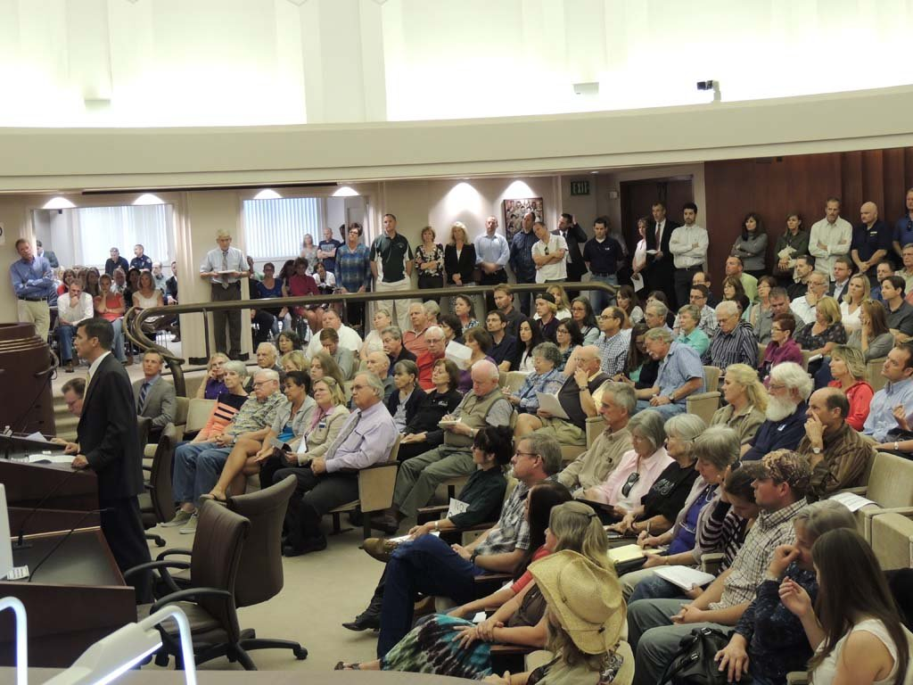 The president of Concordia Homes, Don Underwood, at podium, speaks before City Council and a crowd of residents opposed to the project. He explained that Safari Highlands Ranch would bring high-end housing to Escondido. Photo by Rachel Stine