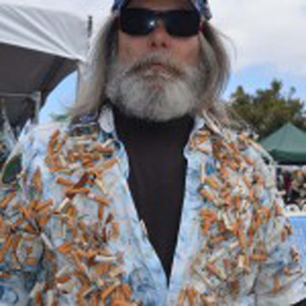 North County resident Robert Nelson makes a fashion and ecological statement with his wardrobe adorned with cigarette butts he's picked up from Oceanside to the Cardiff Kook statue. When he was 8 years old, his father told him it was just as bad to step over trash as it was to litter. He said picking up the cigarette butts was the best thing he could do to help the community. Photo by Tony Cagala