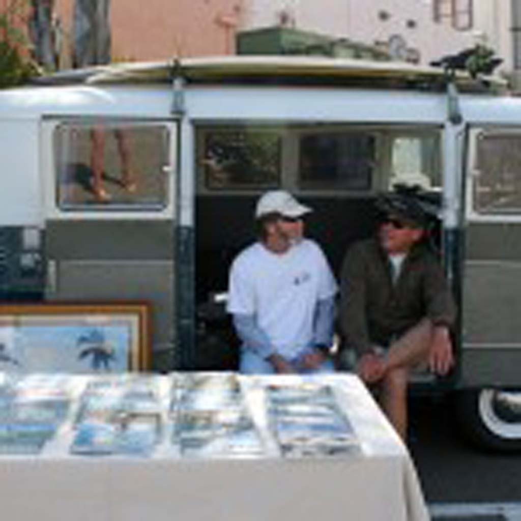 Venders sell out of a Volkswagen van. Vintage surfboards, surf magazines, and art are for sale. Photo by Promise Yee