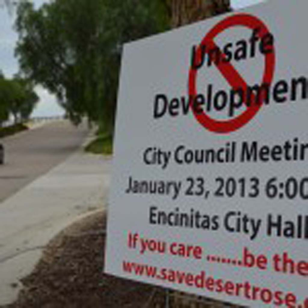 """A sign last year advocates against the """"Desert Rose"""" development in Olivenhain. A Superior Court judge recently ruled the project developer must complete an environmental impact report. Doing so would shrink the project's footprint, those opposed to the project believe. File photo by Jared Whitlock"""