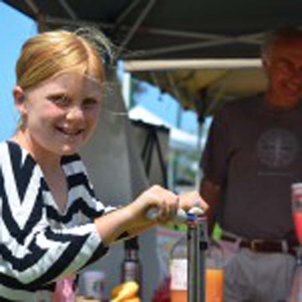 Kira Mawer, 8, blends a smoothie for her family using the power she generated by pedaling a bike. Dadla Ponizil, background, with the Citizens Climate Lobby hosts the blending station and educates people on climate change, saying it's not too late to fix it.