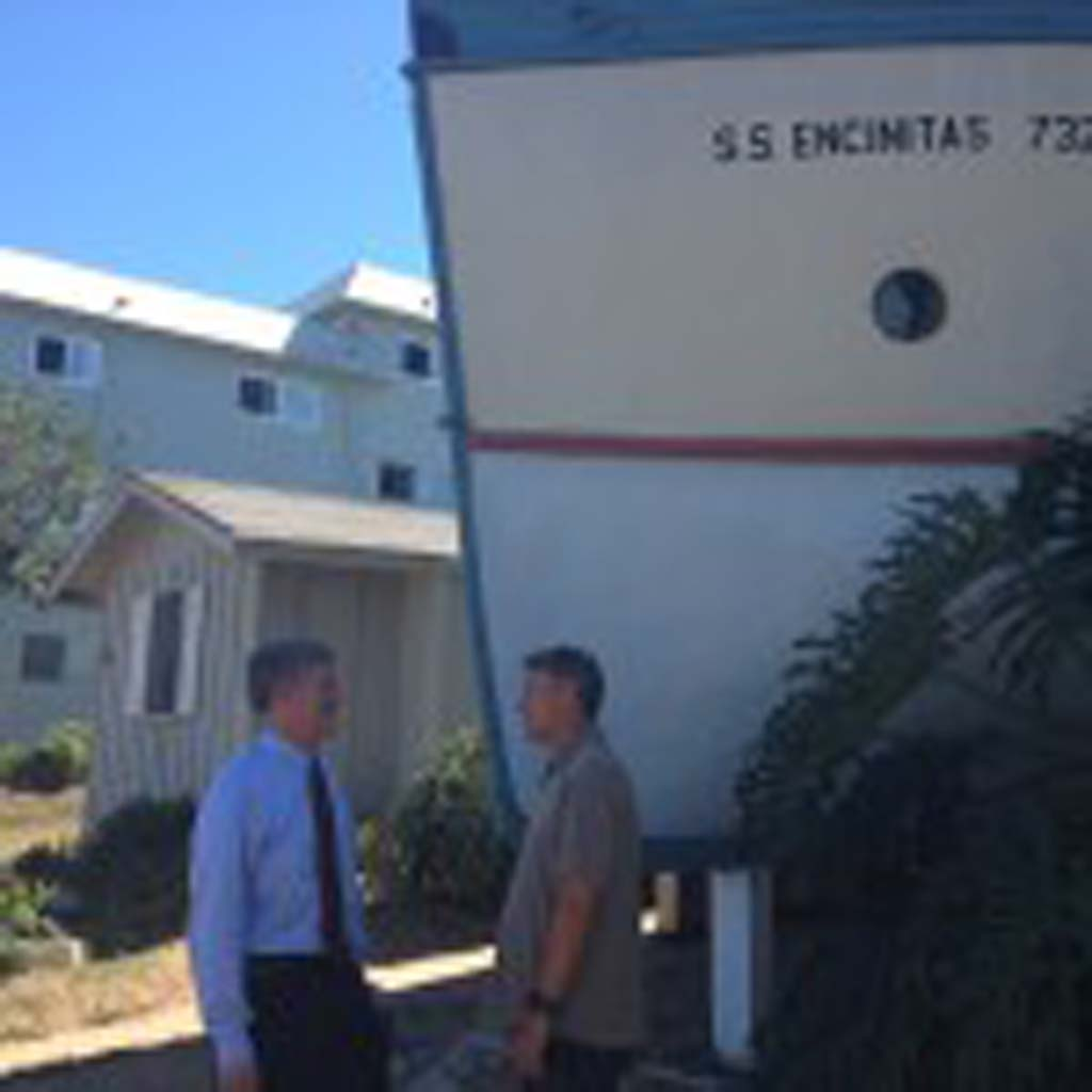 San Diego County Supervisor Dave Roberts, left, talks with Tom Cozens, founder of the Encinitas Preservation Association on Tuesday outside the well-known boathouses in Encinitas. Photo by Aaron Burgin