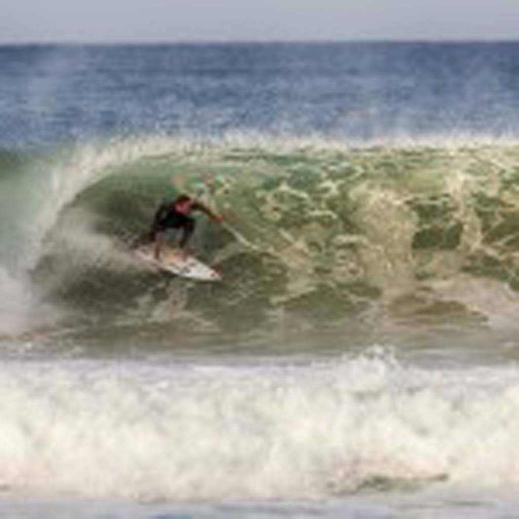 Carlsbad resident and surfer Taylor Knox takes advantage of high surf on Sunday. Photo by Bill Reilly
