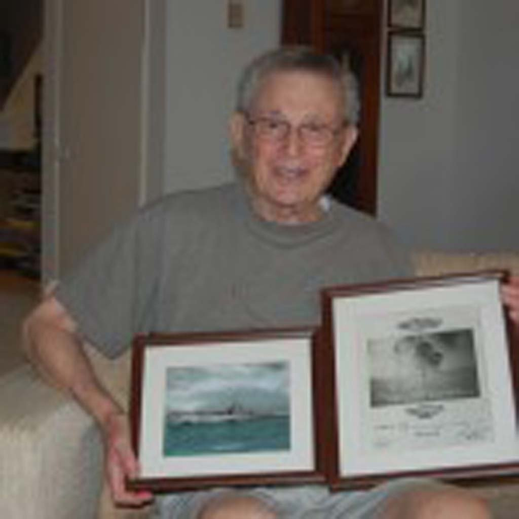 Seymour Phillips, 89, displays some of his World War II photos. The one on the right shows a Japanese freighter following two torpedo hits from the USS Billfish, on which Phillips served. Photo by Bianca Kaplanek