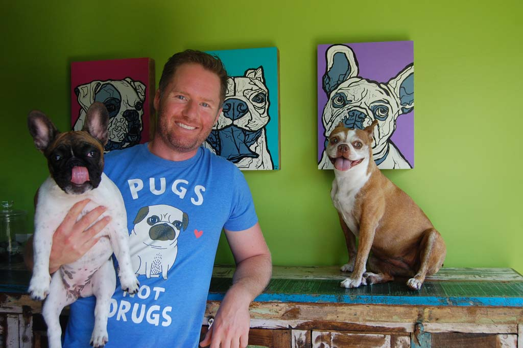 """Todd Murphy will display his """"smush-faced dogs"""" paintings at ArtWalk NTC @ Liberty Station Aug. 16 and Aug. 17. He's seen here with Dempsey, left, and Frances, two of his four dogs whose portraits adorn the wall behind him in his Solana Beach home. Photo by Bianca Kaplanek"""