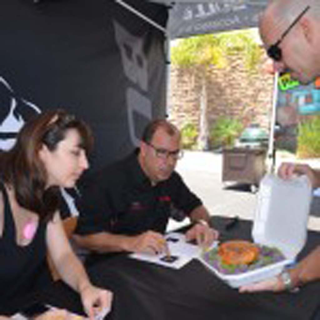 Erin Jackson, left, food writer with San Diego Eats and Bull Outdoor Products, Inc. President Mark Nureddine view one of the burger entries. Photo by Tony Cagala