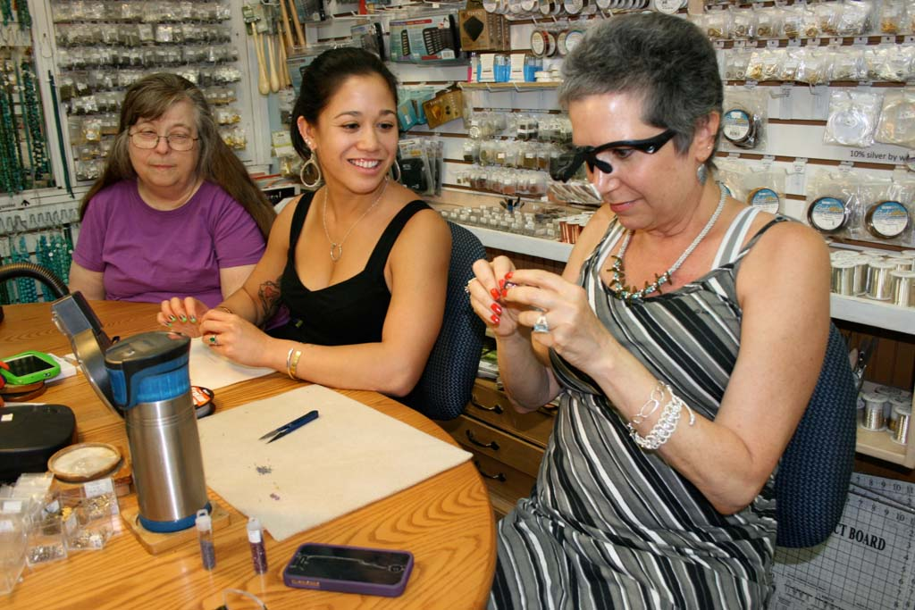Sitting left to right, shop owner Dee Layden, manager Sammi Dulay, and avid beader Rhonda Bloom, of Encinitas, working on their craft. Ocean Sky Beads will close in October. Photo by Promise Yee
