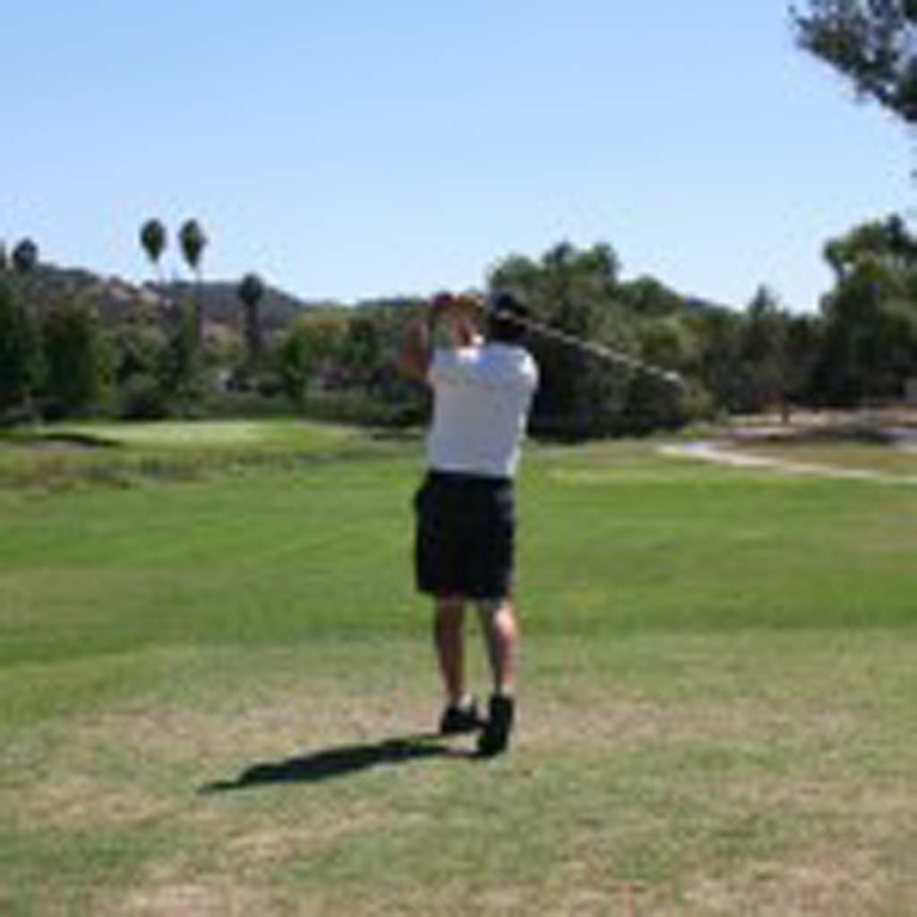 A golfer tees off at the San Luis Rey Downs Golf Course before it closed in August. The property may be turned into a land bank. File photo by Promise Yee