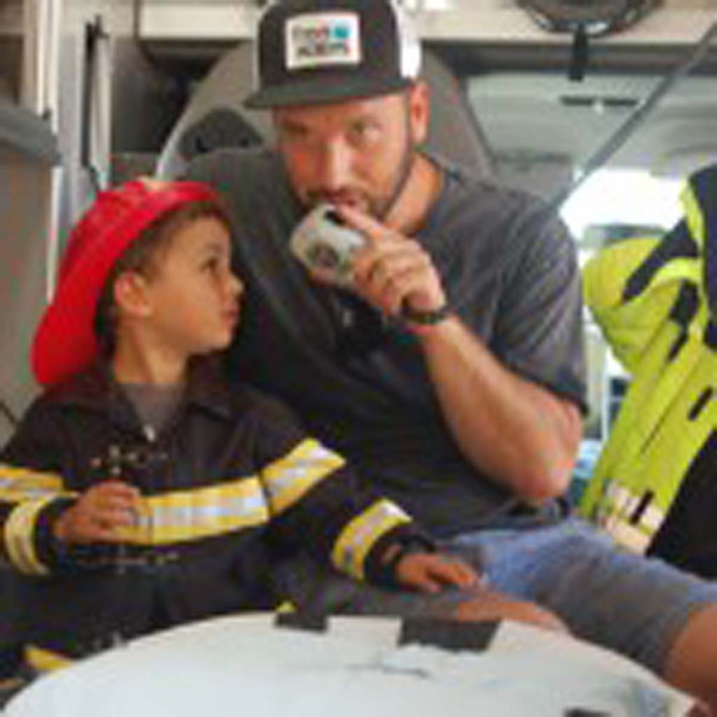 It isn't clear which Leucadia resident is having more fun checking out the equipment on this emergency vehicle — Noah Marmar or his dad, Eli. Photo by Bianca Kaplanek