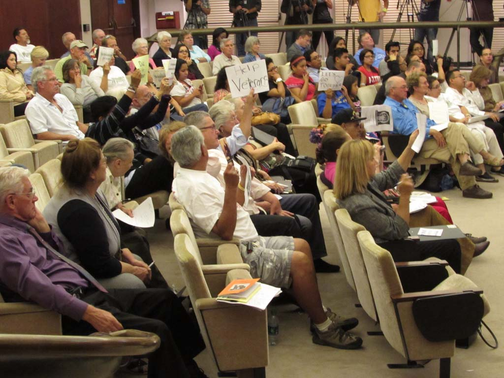 The packed chambers grew heated at times, with people from both sides of the argument holding signs stating their position. Before the meeting even started, police were called into the chambers because of people yelling at each other. Photo by Ellen Wright