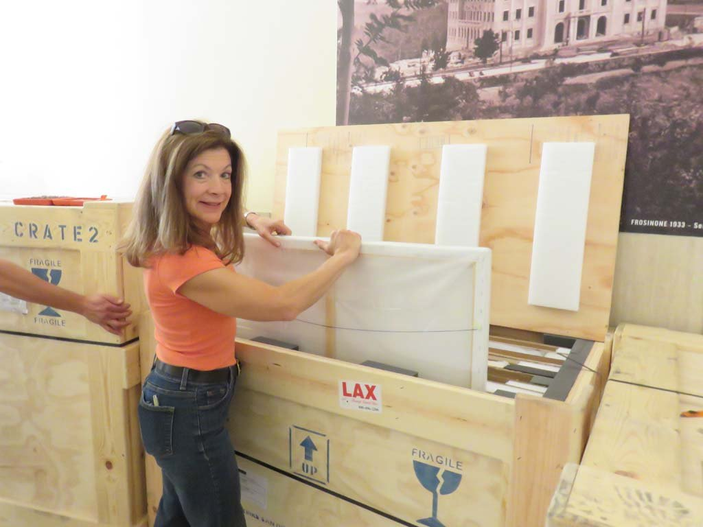 Kay Colvin begins unloading the first of four crates containing the California Dreaming exhibition artwork prior to installation in the Palazzo della Provincia in Frosinone, Italy. Courtesy photo