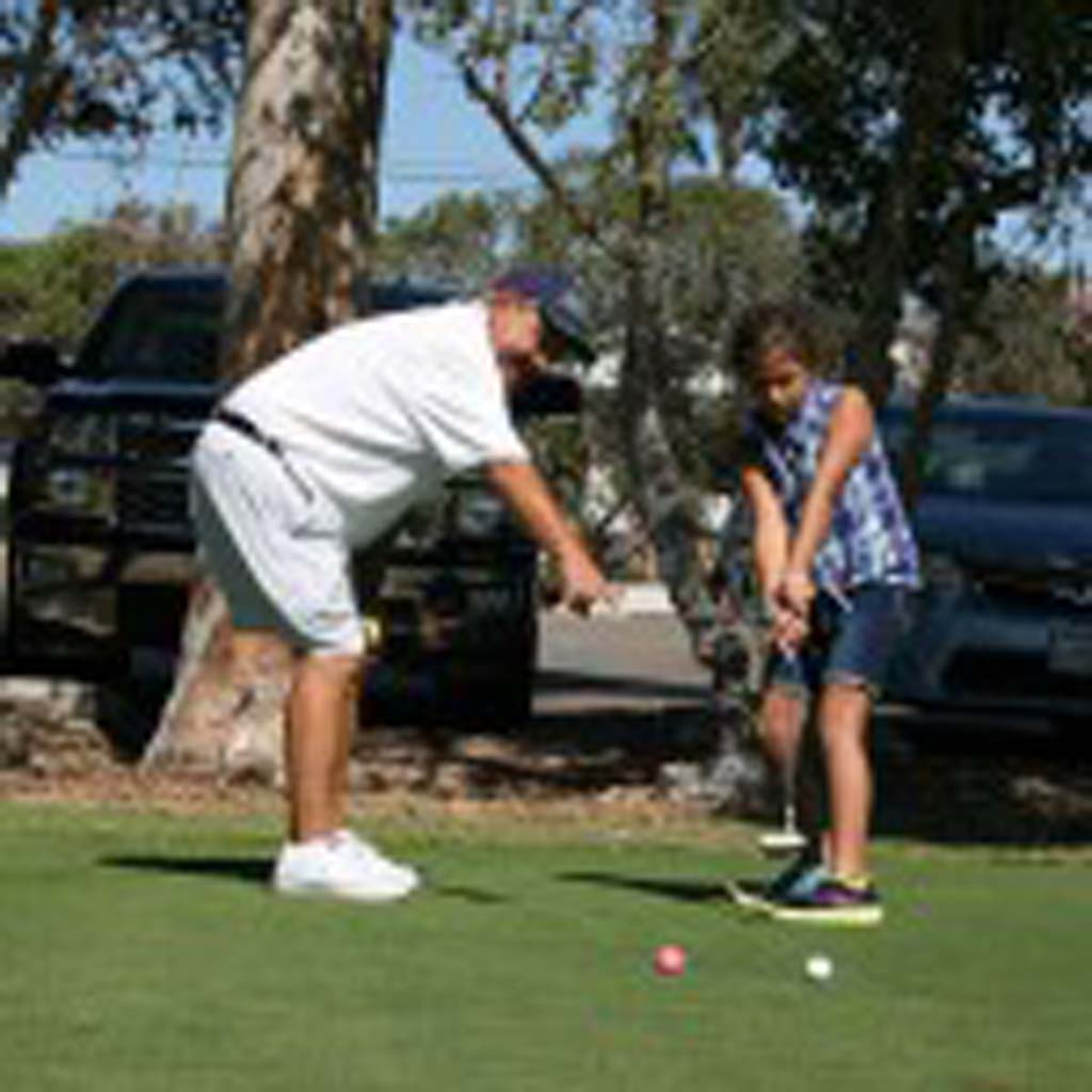PGA golf pro Tito Hualde, left, holds a lesson with Ilima Haupu, 8, of Vista. The golf course is home to the North County Junior Golf Association. Photo by Promise Yee
