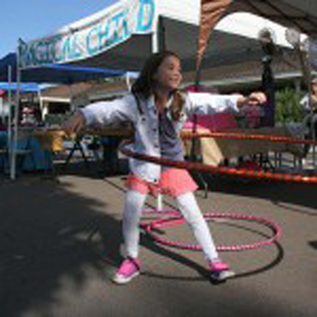Pia Dooley, 8, of San Marcos, tries out a hula-hoop. The Kids Zone has hands-on activities for kids. Photo by Promise Yee
