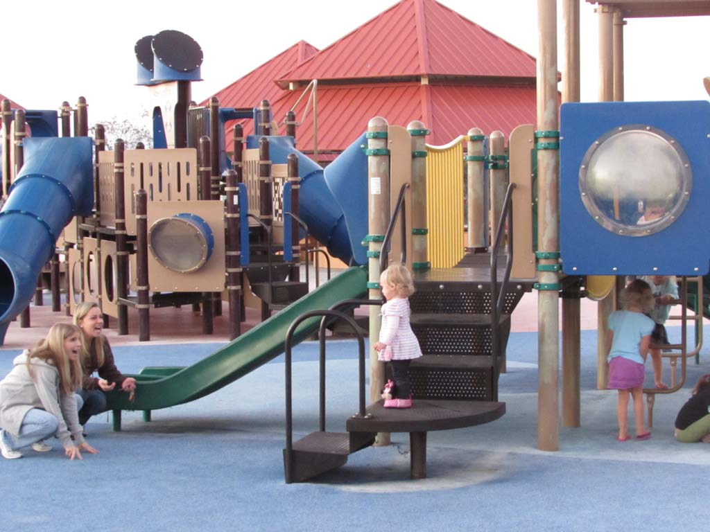 Residents wanted more playgrounds so officials chose to relocate and add another play set at Poinsettia Community Park. Mary and Dawn Wilson play with Aubree Wilson at Aviara Community Park. Photo by Ellen Wright