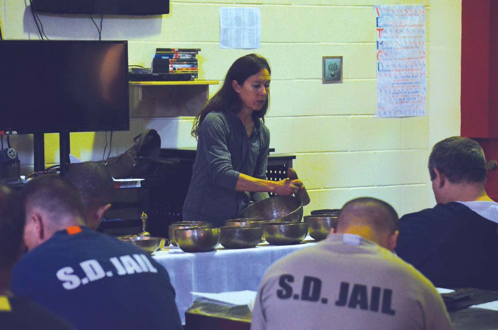Diáne Mandle creates a tone from a Tibetan singing bowl for military veteran inmates at the Veterans Unit of the Vista Detention Facility. Mandle visits the facility every other week to help the inmates learn meditation techniques and get them see themselves in better light. Photo by Tony Cagala