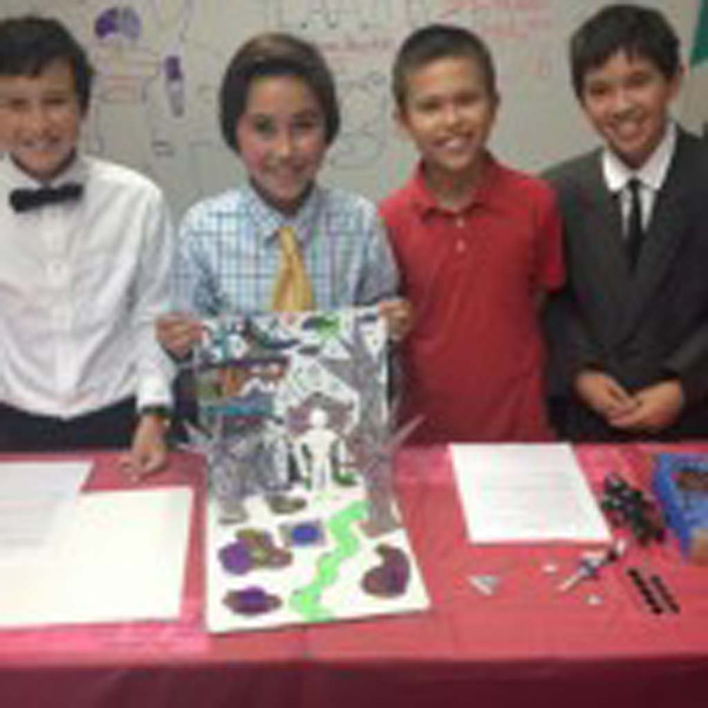 """From left: Luke Kleinrath, Alexander Poroy, Daniel Gurholt and Adam Olander showcase their project during Ada Harris School's second annual Toy Fair. The team created an action figure called """"Legends of Jhiaxus."""" Photo by Aaron Burgin"""