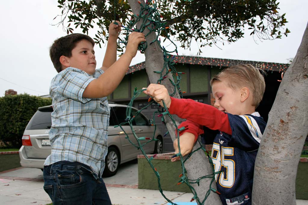 Dakota Benner, 7, left, and Brennan Helper, 6, decorates an outdoor tree. A holiday house-decorating contest is planned to bring the community together. Photo by Promise Yee