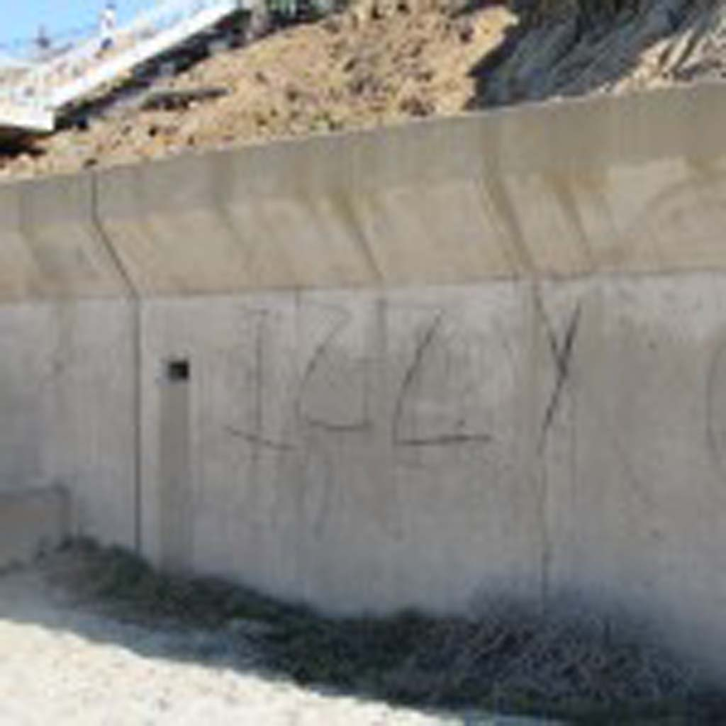 Charcoal graffiti on the seawall in Carlsbad has raised concern. It's particularly prevalent on the seawall north of the Encina Power Station, according to Beach Preservation Committee member Fred Briggs. Photo by Ellen Wright