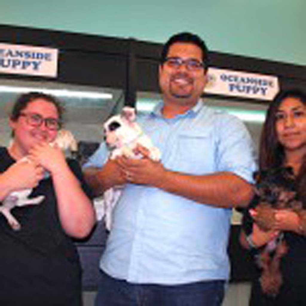 Oceanside Puppy owner David Salinas, center, said he would pursue legal action against the city. An Oceanside ordinance will close Oceanside Puppy unless the owner complies. File photo by Promise Yee