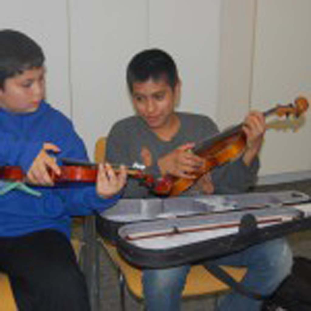 Alex Monory, left, helps teach Juel Taiea to play the viola during an after-school San Diego Youth Symphony and Conservatory music program at Casa de Amistad. Photo by Bianca Kaplanek