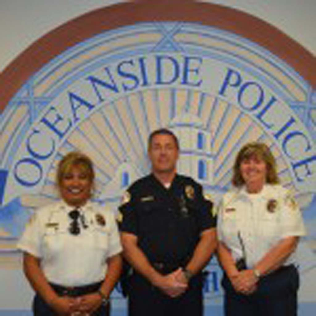 Oceanside Senior Volunteer Police Patrol members Francesca Johnson, left, and Melodie Burch, with Matt Christensen, field operation support sergeant overseeing the senior volunteer police patrol, center, at the Oceanside Police Department. The patrol is seeking more members to help with the services it provides to the community and police department. Photo by Tony Cagala