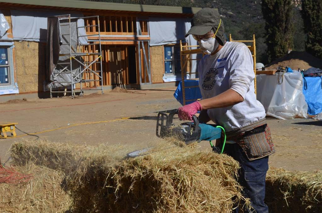 A chainsaw is used to cut into a straw bale that will eventually be placed into the wooden frames and become the walls of new housing for the Zen Buddhist nuns at Deer Park Monastery in Escondido. Photo by Tony Cagala