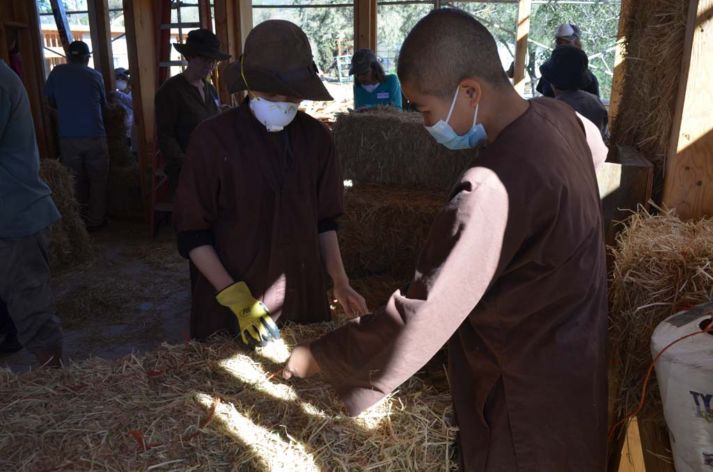 Zen Buddhist nuns at Deer Park Monastery help to build their new homes using straw bales. Photo by Tony Cagala
