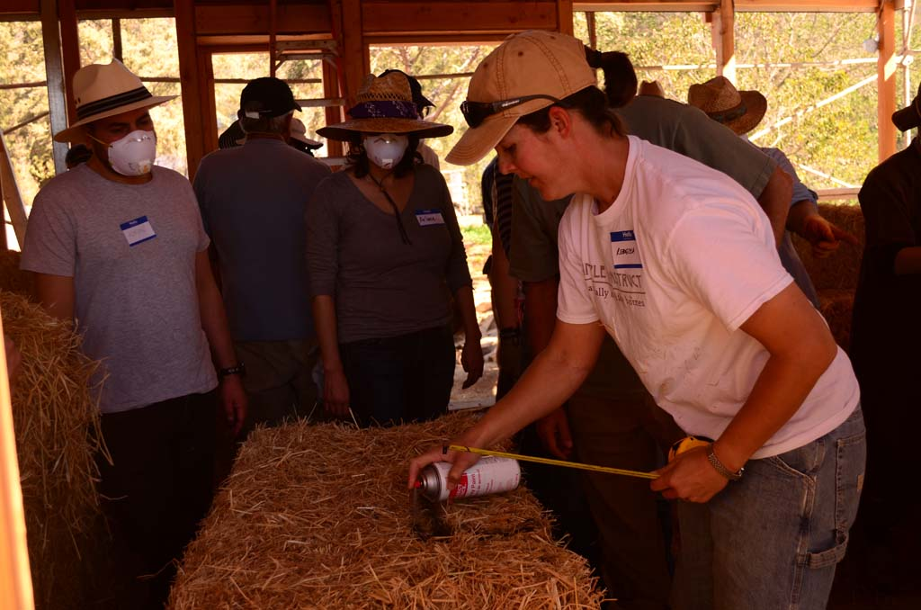 Rebecca Tasker, right, co-owner of Simple Construct, working with dozens of volunteers, makes some measurements on a straw bale. Photo by Tony Cagala